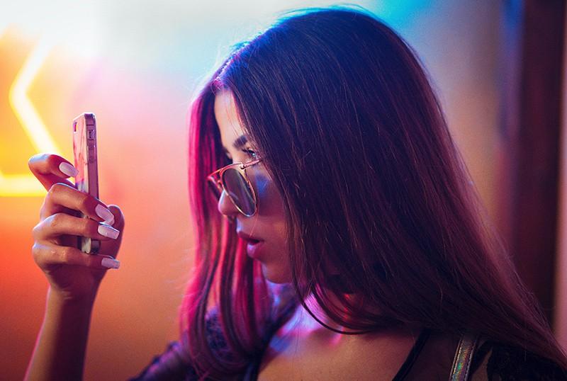 eine Frau, die Smartphone beim Lesen einer Nachricht betrachtet