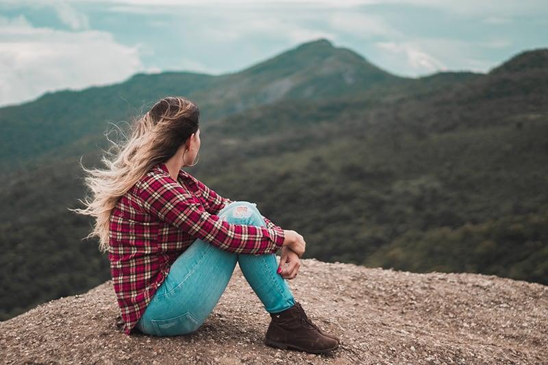eine Frau, die alleine auf dem Boden sitzt und einen Hügel überblickt, während sie nachdenkt
