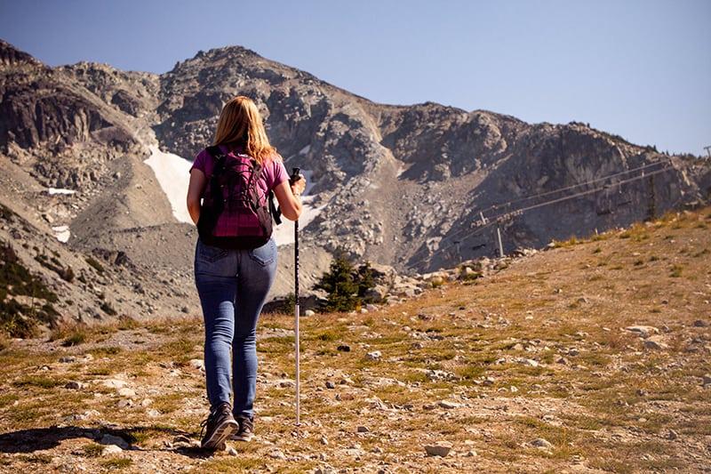 eine Frau, die auf einer Wiese mit Blick auf die Berge geht