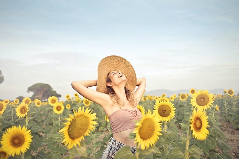eine Frau, die auf Sonnenblumenfeld steht und das Leben genießt