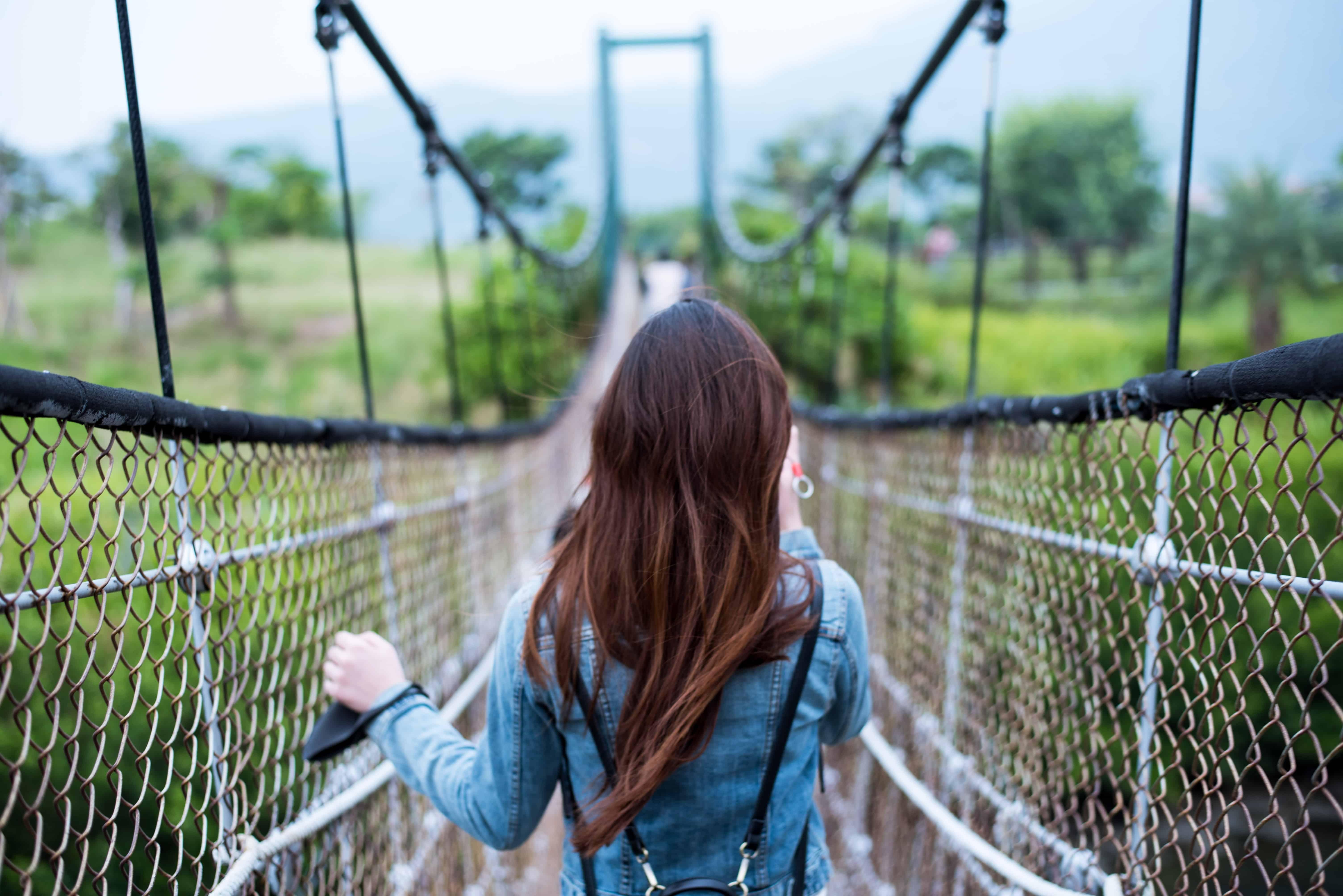 eine Frau, die auf einer Hängebrücke steht, die den Bergen gegenübersteht
