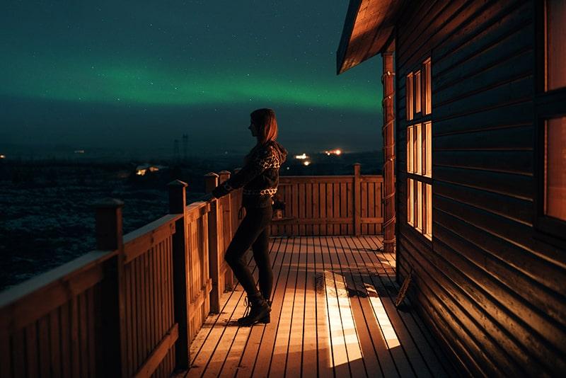 eine Frau, die nachts auf einer Terrasse steht