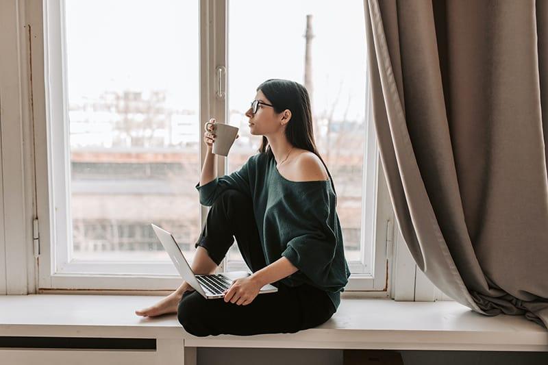 Eine Frau, die beim Kaffeetrinken neben dem Fenster nachdachte