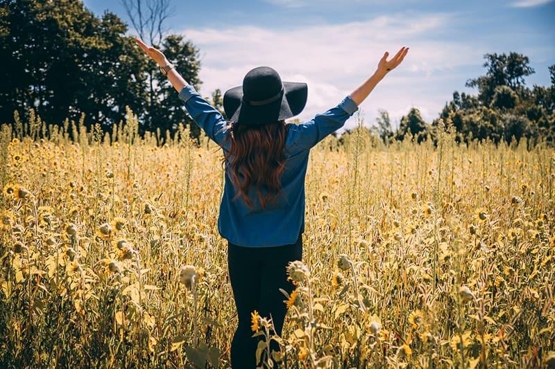 eine Frau, die dankbar ist, ihre Arme zu heben, während sie auf dem Feld steht