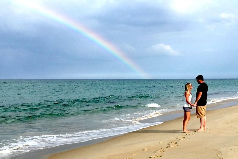 eine Frau, die die Hand eines Mannes hält, während sie an der Küste mit ihm spricht