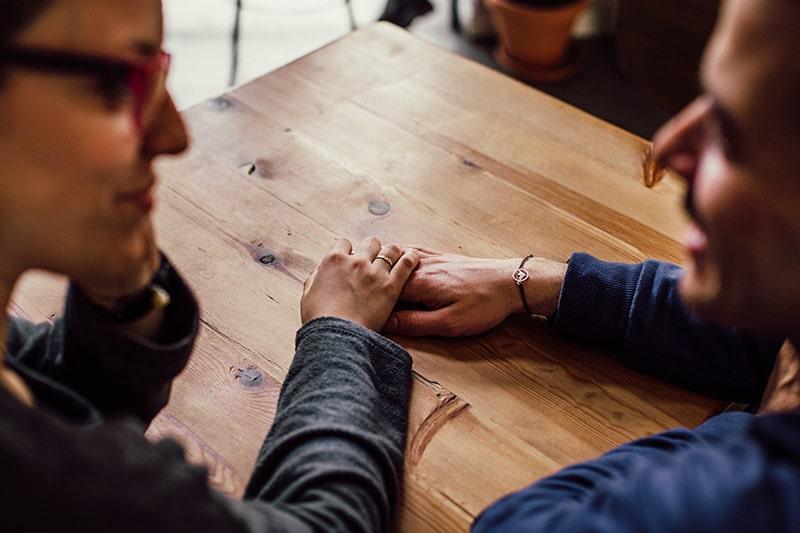 eine Frau, die die Hand eines Mannes hält, während sie zusammen am Tisch sitzt