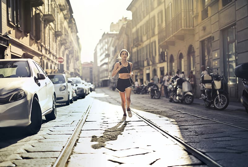 eine Frau, die die Straße entlang joggt, während sie Musik über Kopfhörer hört