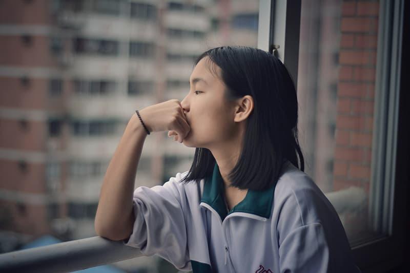 eine Frau, die beim Nachdenken durch das Fenster schaut