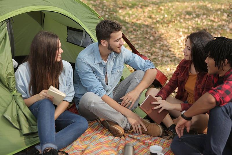 eine Frau, die ein Buch hält, das einen Mann betrachtet, während sie mit Freunden im Lager sitzt