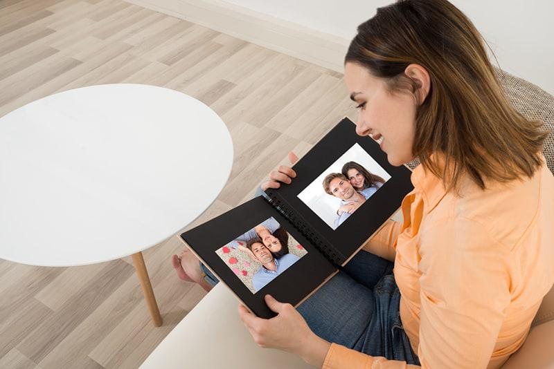 eine Frau, die ein Fotoalbum mit Fotos von sich und ihrem Freund sucht