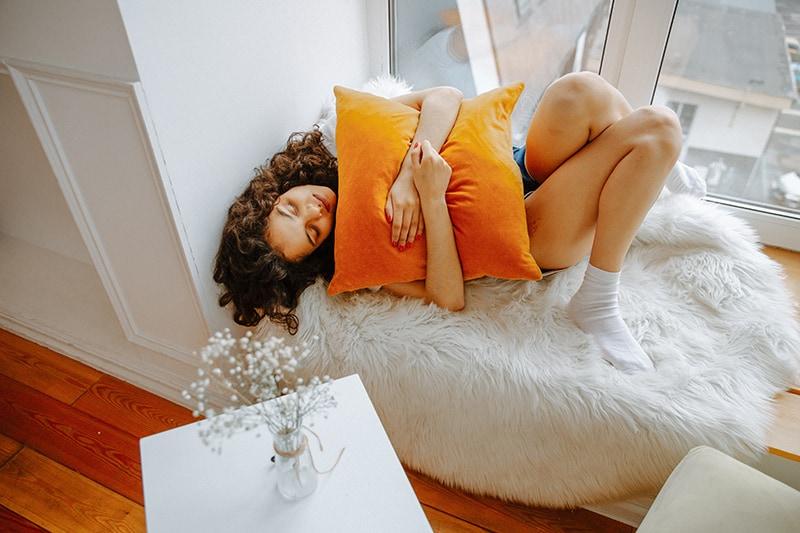 eine Frau, die ein Kissen umarmt, während sie in der Nähe des Fensters liegt