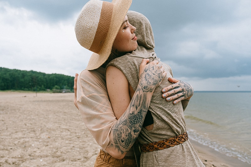 eine Frau, die eine Freundin tröstet, während sie an der Küste steht