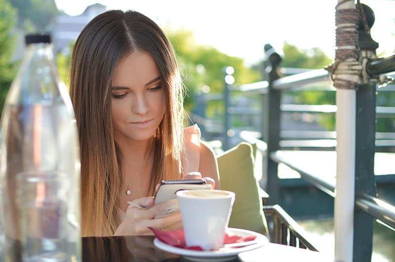 eine Frau, die eine Kontaktliste auf einem Smartphone betrachtet, während sie alleine in der Cafeteria sitzt