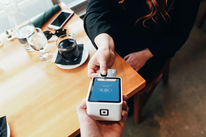 eine Frau, die eine Rechnung mit einer Kreditkarte bezahlt in der Cafeteria