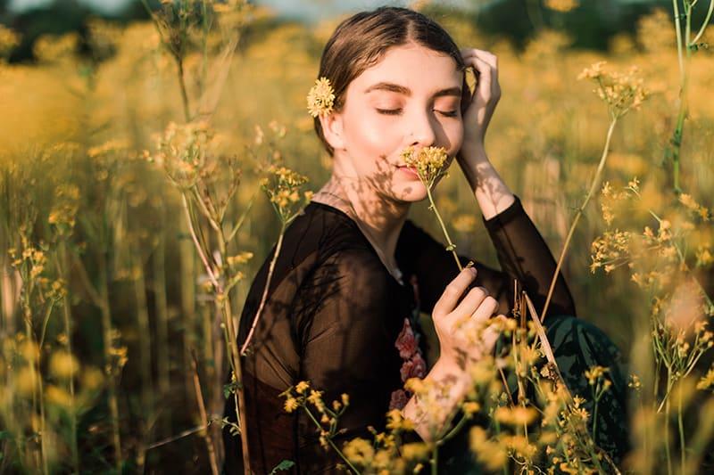 eine Frau, die eine gelbe Blume auf dem Feld riecht