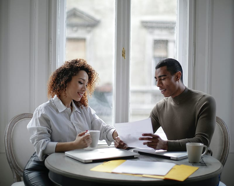 eine Frau, die einem Mann hilft, seine Arbeit zu erledigen, während er zusammen am Tisch sitzt