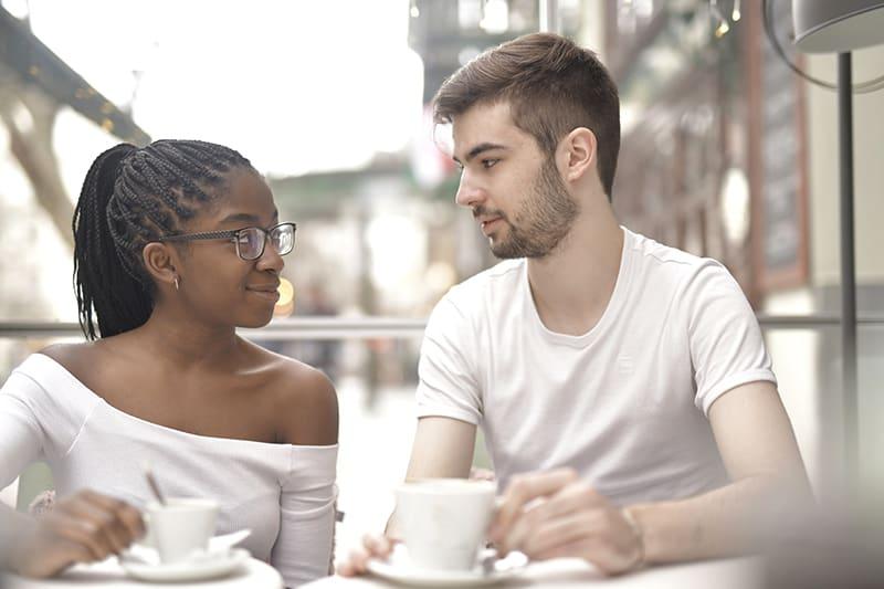 eine Frau, die einem Mann mit Respekt zuhört, während sie zusammen Kaffee trinkt