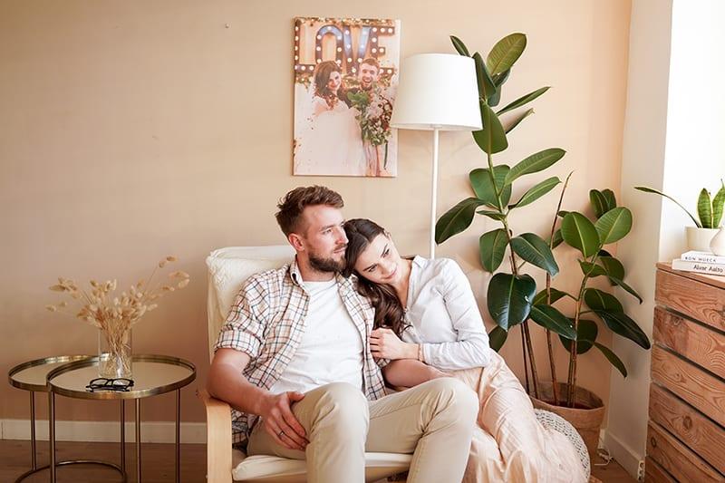 eine Frau, die einen Mann umarmt, während beide in einem Sessel sitzen und zur Seite schauen
