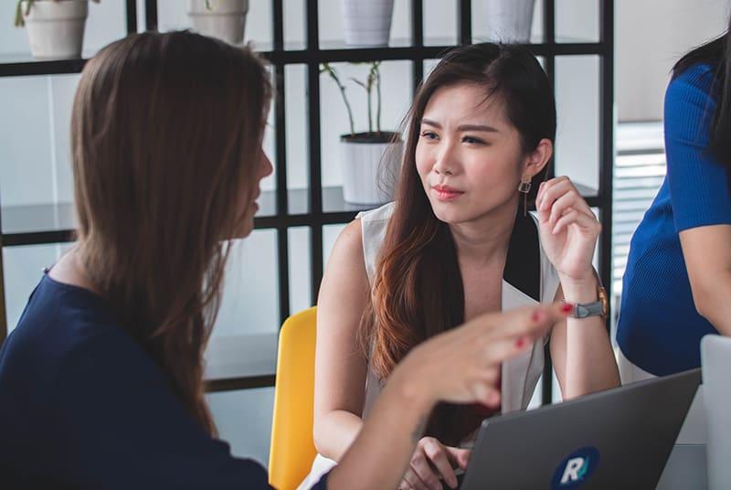 eine Frau, die einer Freundin zuhört, während beide vor einem Laptop sitzen