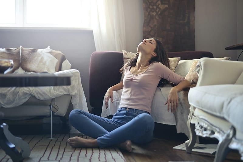 eine Frau, die ihren Körper entspannt, während sie auf dem Boden sitzt und sich auf das Sofa lehnt