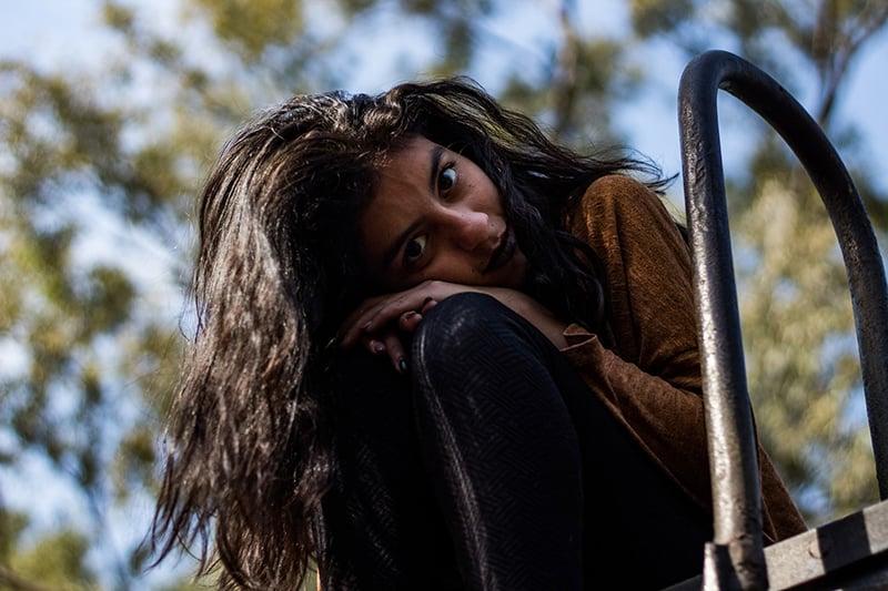 Eine Frau lehnte ihren Kopf auf die Knie, während sie in der Nähe der Metallleiter saß