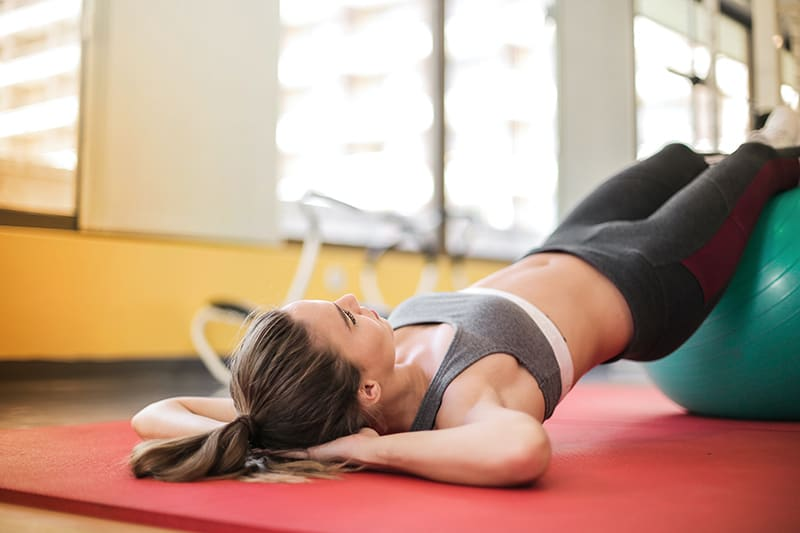 eine Frau, die im Fitnessstudio auf der Matte liegt