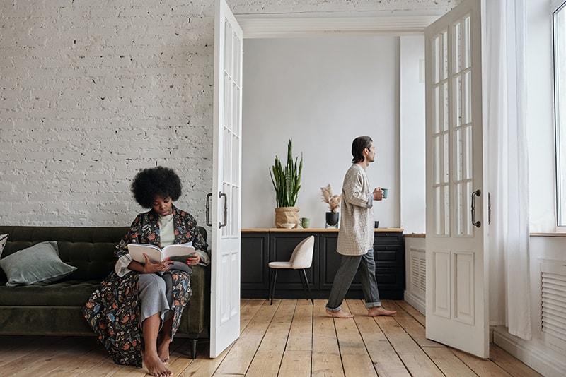 Eine Frau liest eine Zeitschrift im Wohnzimmer und ein Mann trinkt Kaffee neben dem Fenster im Nebenzimmer
