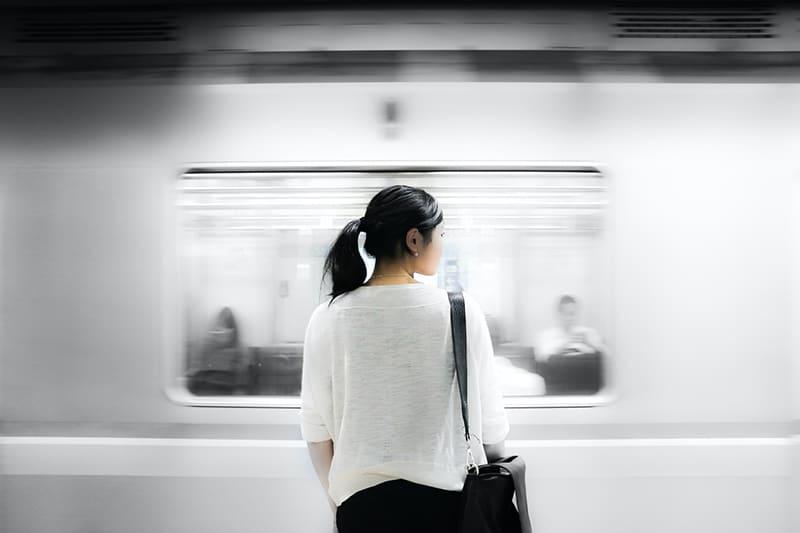eine Frau, die in der Nähe eines Zuges in einer U-Bahn steht