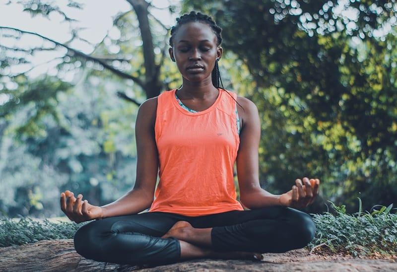 eine Frau, die in der Natur meditiert, während sie auf dem Boden sitzt
