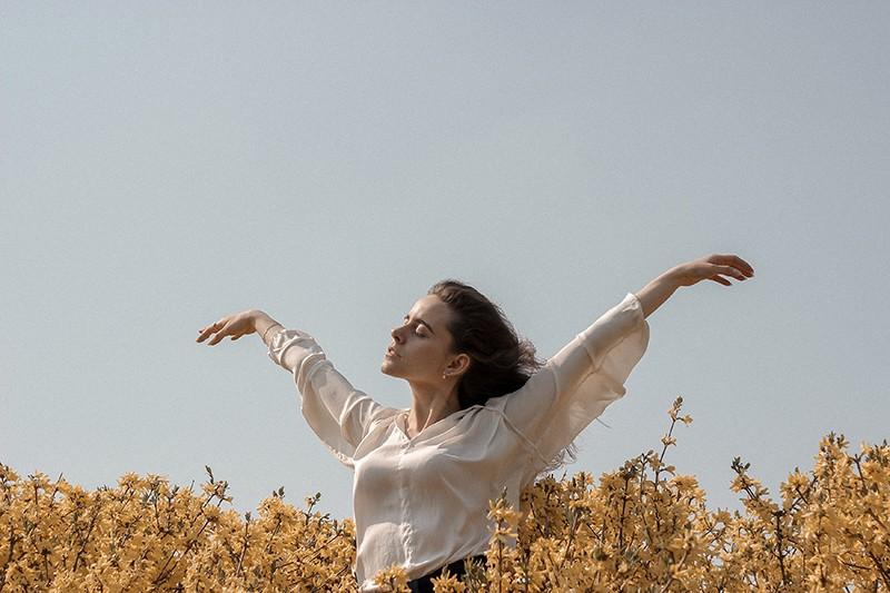 eine Frau, die in einem Blumenfeld steht, während Arme ausbreitet