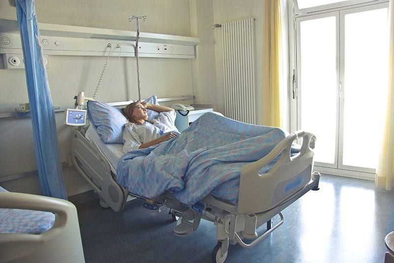 eine Frau, die in einem Krankenhausbett liegt und das Fenster betrachtet