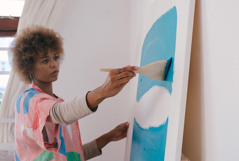 eine Frau, die mit blauer Farbe auf Leinwand malt, um ihre Gedanken abzulenken