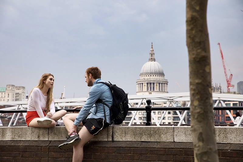 eine Frau, die mit einem Mann spricht, während er auf der Betonwand sitzt