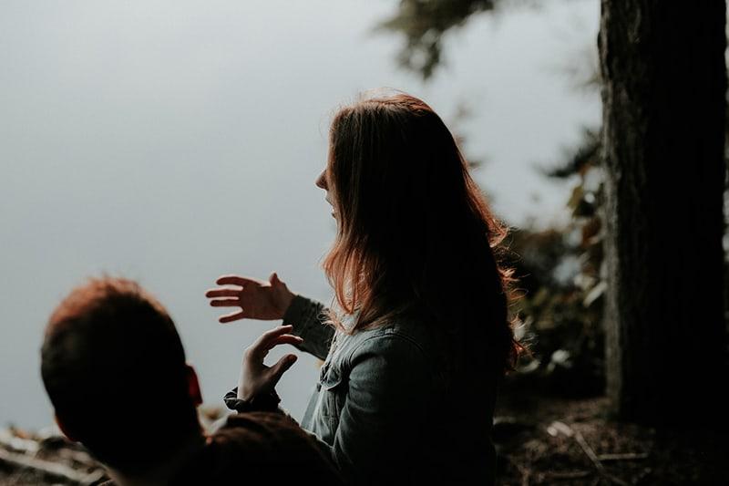 eine Frau, die mit einem Mann spricht, während sie mit ihren Händen gestikuliert