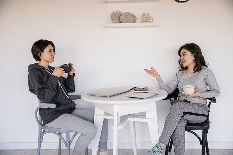 eine Frau, die mit einem launischen Freund spricht, während er Kaffee trinkt