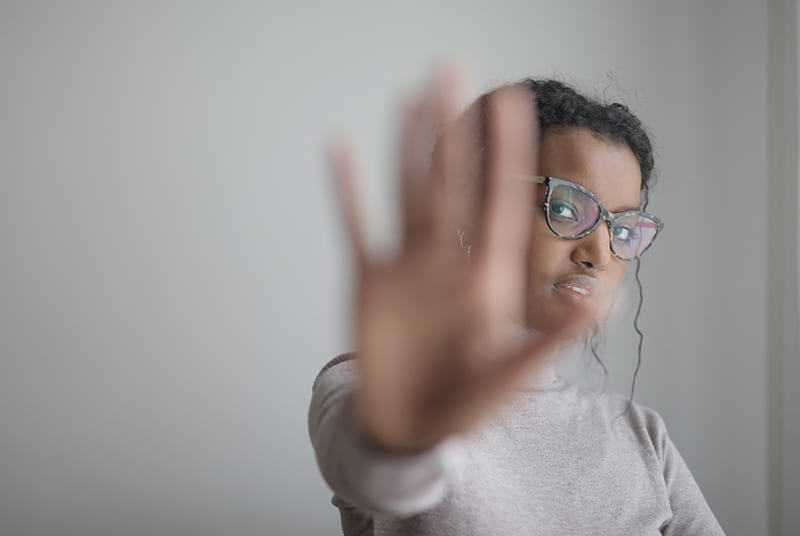 eine Frau, die Stoppgeste mit einer Handfläche tut, während sie nahe grauer Wand steht
