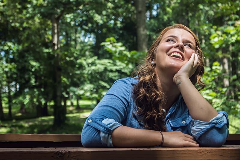 eine Frau, die sich während der Fantasien auf den Holzzaun stützt