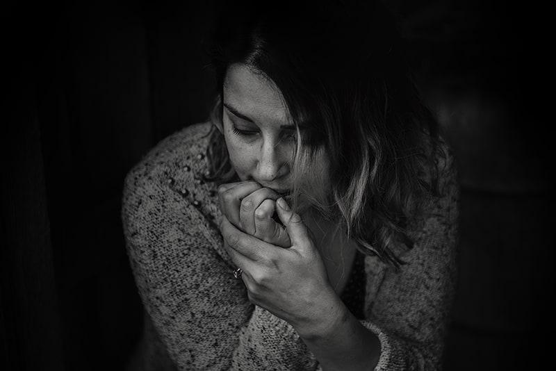 eine Frau, die sich schuldig fühlt und ihre Lippen mit der Hand berührt