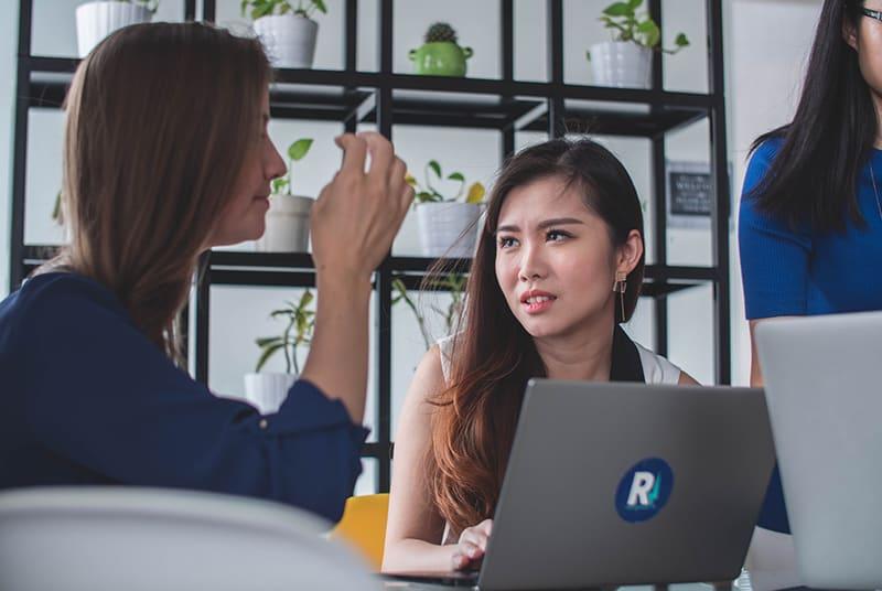 eine Frau, die verwirrt aussieht und zu einem Kollegen schaut, während sie vor einem Laptop sitzt