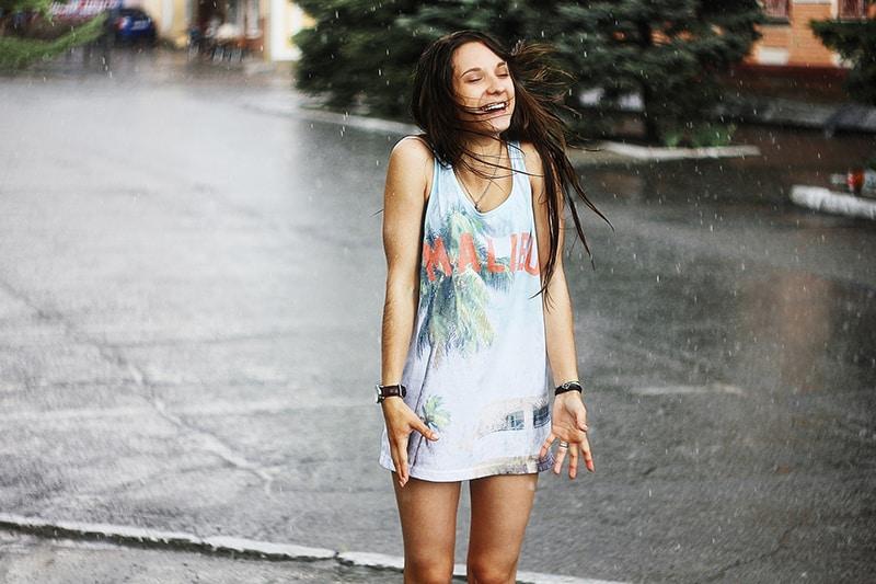 eine Frau, die im Regen steht und glücklich aussieht