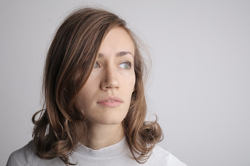 eine Frau im weißen Hemd, die beiseite schaut, während sie nahe der Wand steht