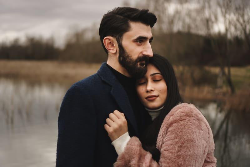 eine Frau in den Armen eines Mannes mit Bart an einem Fluss