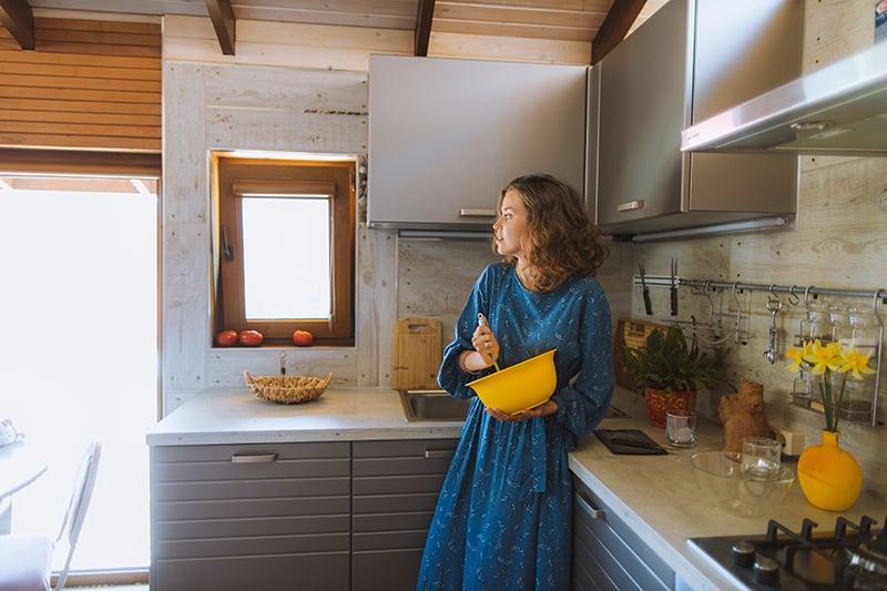 eine Frau in einem blauen Kleid, die in der Küche steht und eine gelbe Schüssel hält