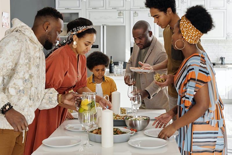 Eine Frau in einem orangefarbenen Kleid deckt mit ihrer Familie den Tisch zum Abendessen