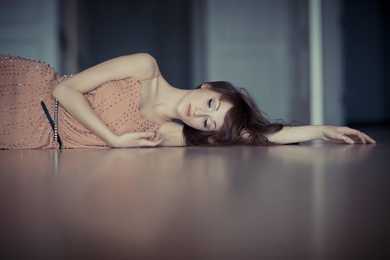 eine Frau in einem orangefarbenen Kleid, das auf dem Boden liegt