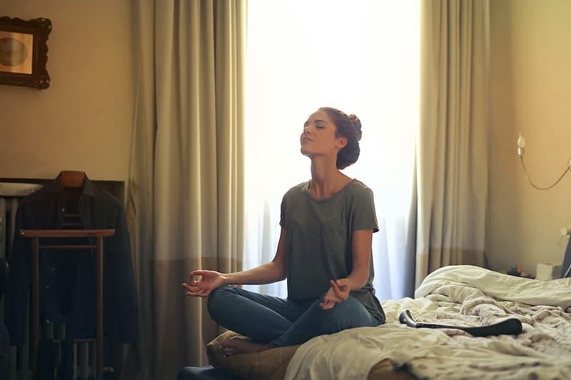 eine Frau meditiert, während sie auf dem Bett im Schlafzimmer sitzt