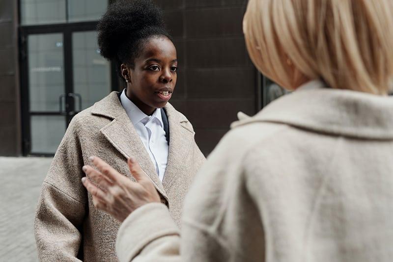 eine Frau mit blonden Haaren, die einer Frau mit schwarzen Haaren etwas erklärt, während sie draußen steht