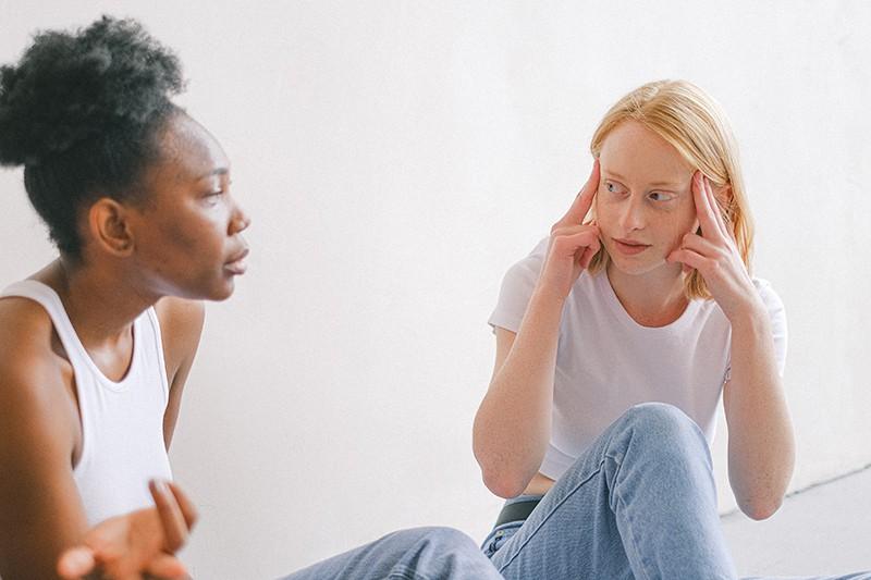eine Frau mit blonden Haaren, die ihren Kopf berührt, während sie neben einer Freundin sitzt