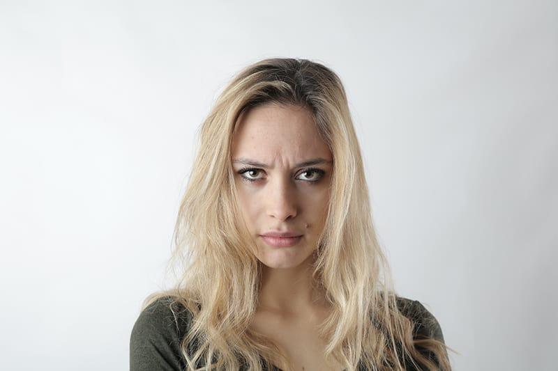 eine Frau mit blonden Haaren, die eifersüchtig aussieht