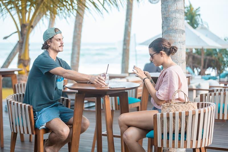 eine Frau, die ein Smartphone benutzt, und ein Mann, der ein Glas hält, während sie in einem Café draußen sitzen